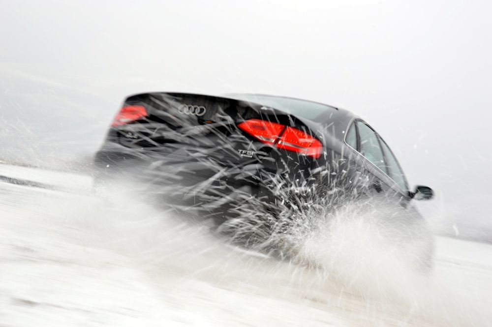 Audi A4 quattro w zimie ze śniegiem spod kół